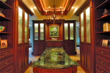 Walk in closet with Mirrors, Glass doors and granite or marble counters